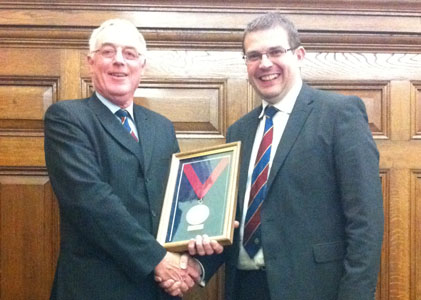 Dave Court (left) receives his medal from new BTS Chairman Damian McGirr