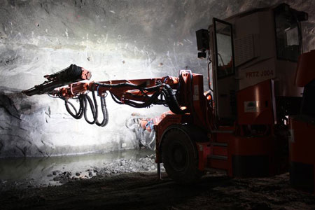 Two twin-boom Sandvik jumbo drill rigs are operating side by side on the 20.5m x 11m tunnel