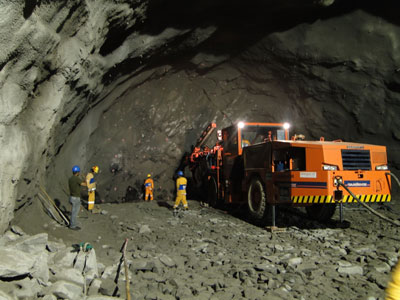 A Sandvik jumbo drill rig (left) and laying the charges (right)