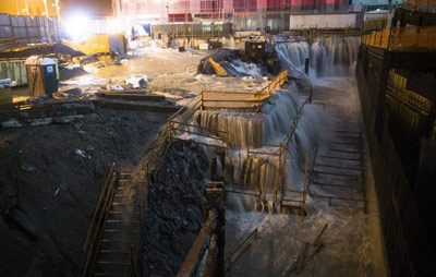 Water pouring into the iconic Ground Zero site (left), and a parking lot of yellow cabs almost submerged (right)