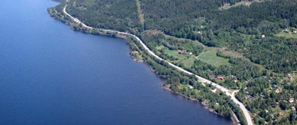E6 highway and Dovrebanen rail line hug the lake shore