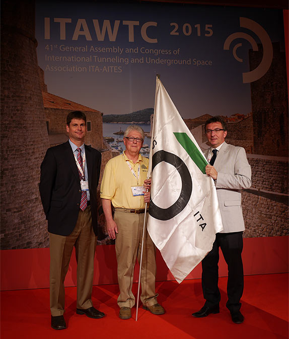 "ITA Croatia President Davorin Kolić (right), passes the ITA banner to Bill Egerton (centre) and Michael Smithson (left), representing the USA, ahead of WTC2016 in San Francisco"" style=""width:255px;"