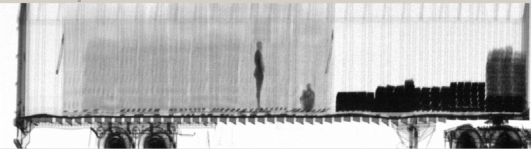 A gamma-ray image shows two international stowaways inside a truck trailer