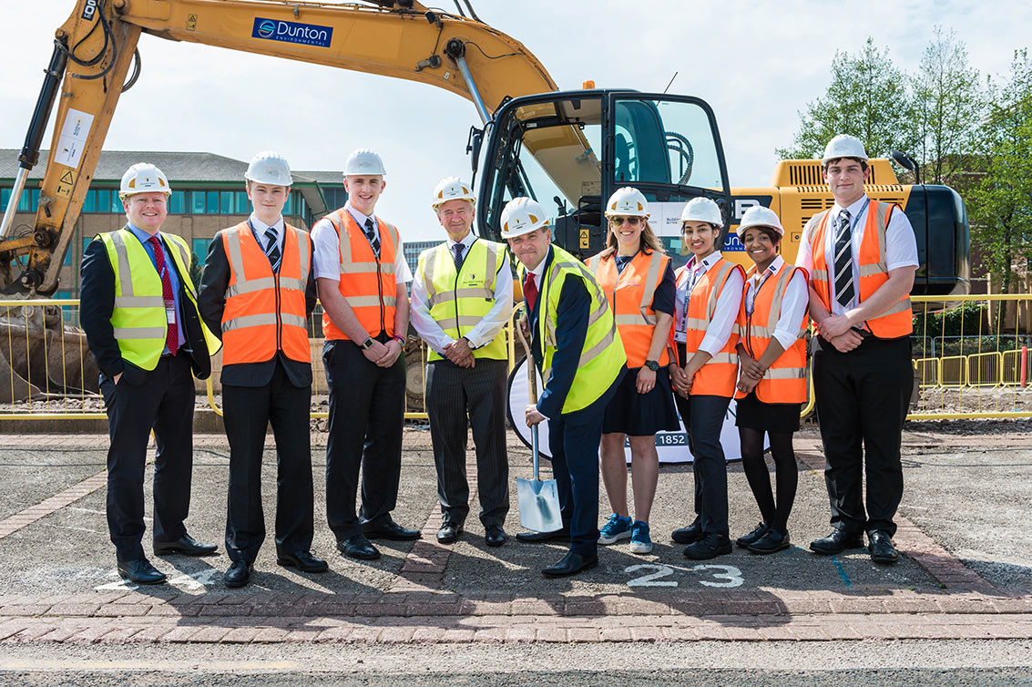Cllr John Clancy (Leader of Birmingham City Council, centre) officially breaks ground with Terry Morgan (Chairman, NCHSR) on his left, Beth West (HS2 Ltd) on his right, and students and staff from Aston University Engineering Academy