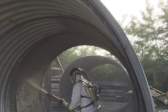 Spraying inside a corrugated pipe
